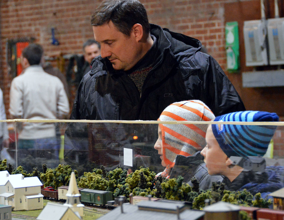 Description of . News-Herald photo — DEBBY HIGH Dave Secor with his 6-year-old son, Noah, and his friend, Lincoln Mann, check out the model train display.
