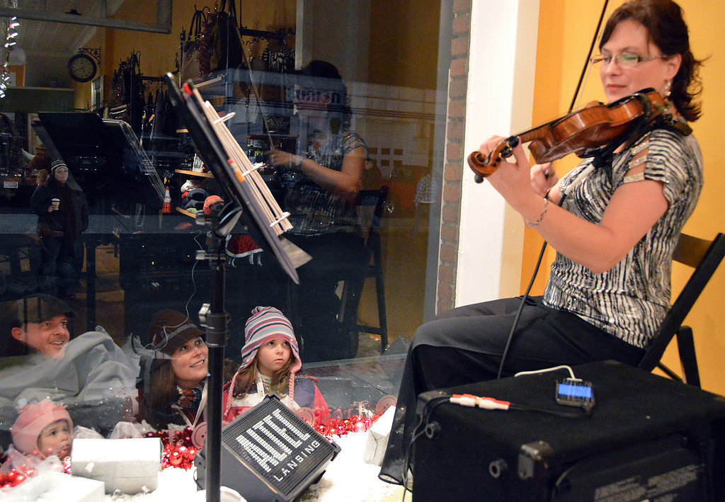Description of . News-Herald photo — DEBBY HIGH The Hackman family, of Salford Township, watch and listen to violinist Deirdre Edgell in the window of FROX.