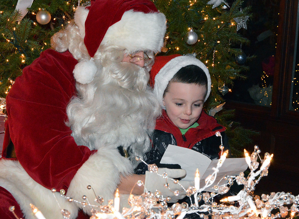 Description of . News-Herald photo — DEBBY HIGH Thane Crossin, 5, gives his list to Santa at the Perkasie tree lighting ceremony Saturday, Dec. 7.