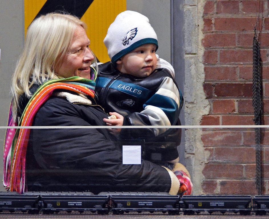 Description of . News-Herald photo — DEBBY HIGH Norma Stock holds her grandson, Charlie Stock III, to watch Doug Kramer's nostalgic holiday train display at the Perkasie Electric Building.