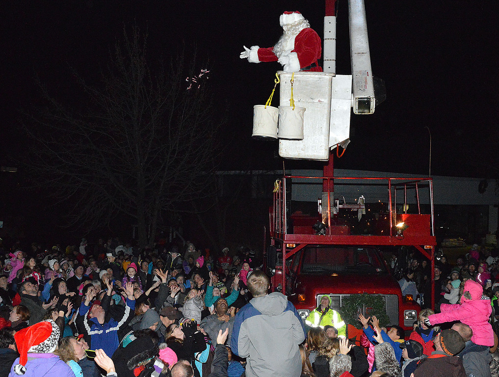 Description of . News-Herald photo — DEBBY HIGH The crowd reaches for candy canes dropped by Santa.