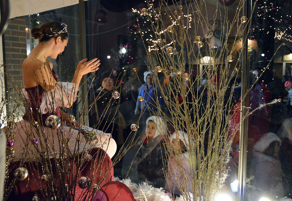"""Description of . News-Herald photo — DEBBY HIGH Catherine Senoyuit, dressed as a """"Sugar Plum Fairy,"""" captures the eyes of the crowd as she stands in a store window."""