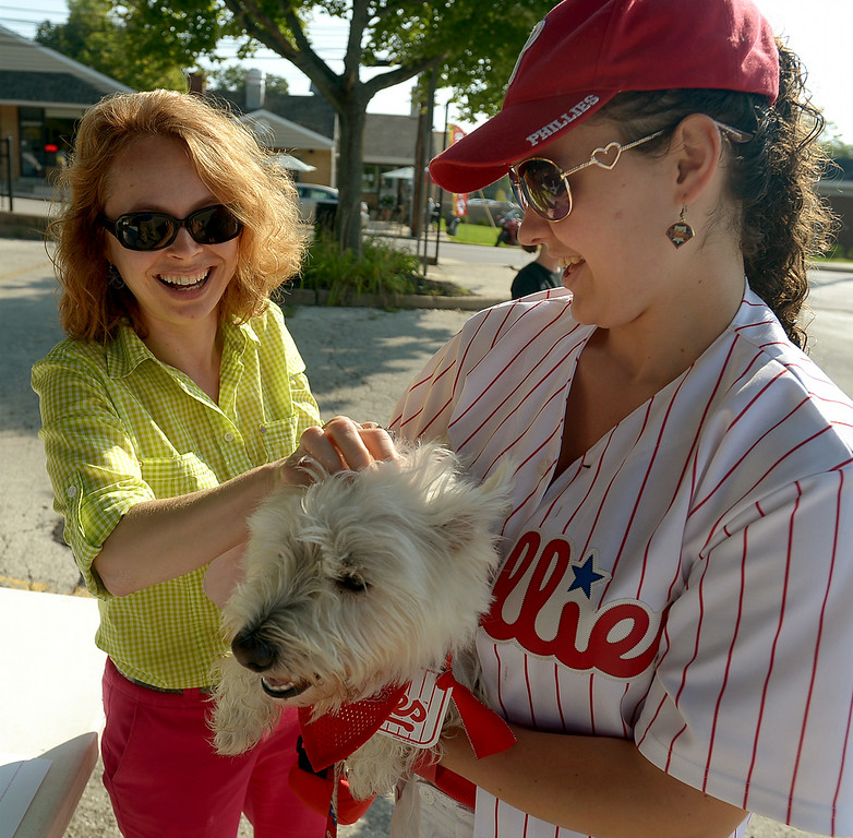 Description of . Mayor Jeanne Sorg, left, ruffles Dante's fur after pinning on the West Highland terrier's registration number for the Ambler Dog Days Parade Saturday, Aug. 9, 2014. Dante belongs to Marilee Gallagher. Montgomery Media staff photo by Bob Raines