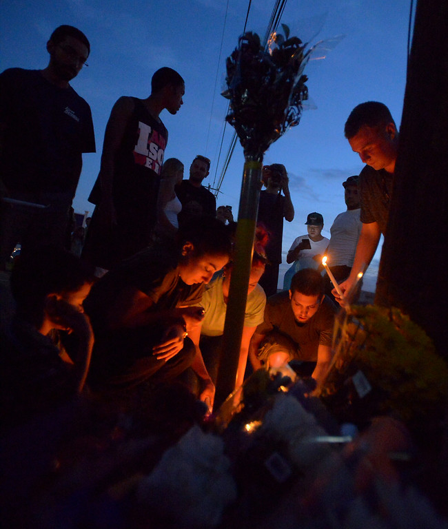 Description of . Mourners light candles Monday night, Aug. 25, 2014 at the site of a fatal crash along Broad St., Montgomery Media staff photo by Bob Raines