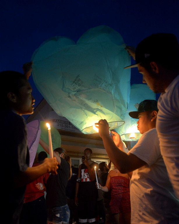 Description of . Pat Pravongviengkham uses a candle to fill one of the  heart-shaped paper hot air balloons which were released Monday night, Aug. 25, 2014 in honor of the victim of a fatal crash on Broad St, Hatfield. Montgomery Media staff photo by Bob Raines