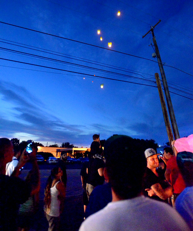 Description of . Mourners watch as heart-shaped hot air balloons float away over Broad St., Hatfield Monday, Aug. 25, 2014. Montgomery Media staff photo by Bob Raines